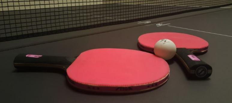2 rote Tischtennis Schläger auf einer schwarzen Platte